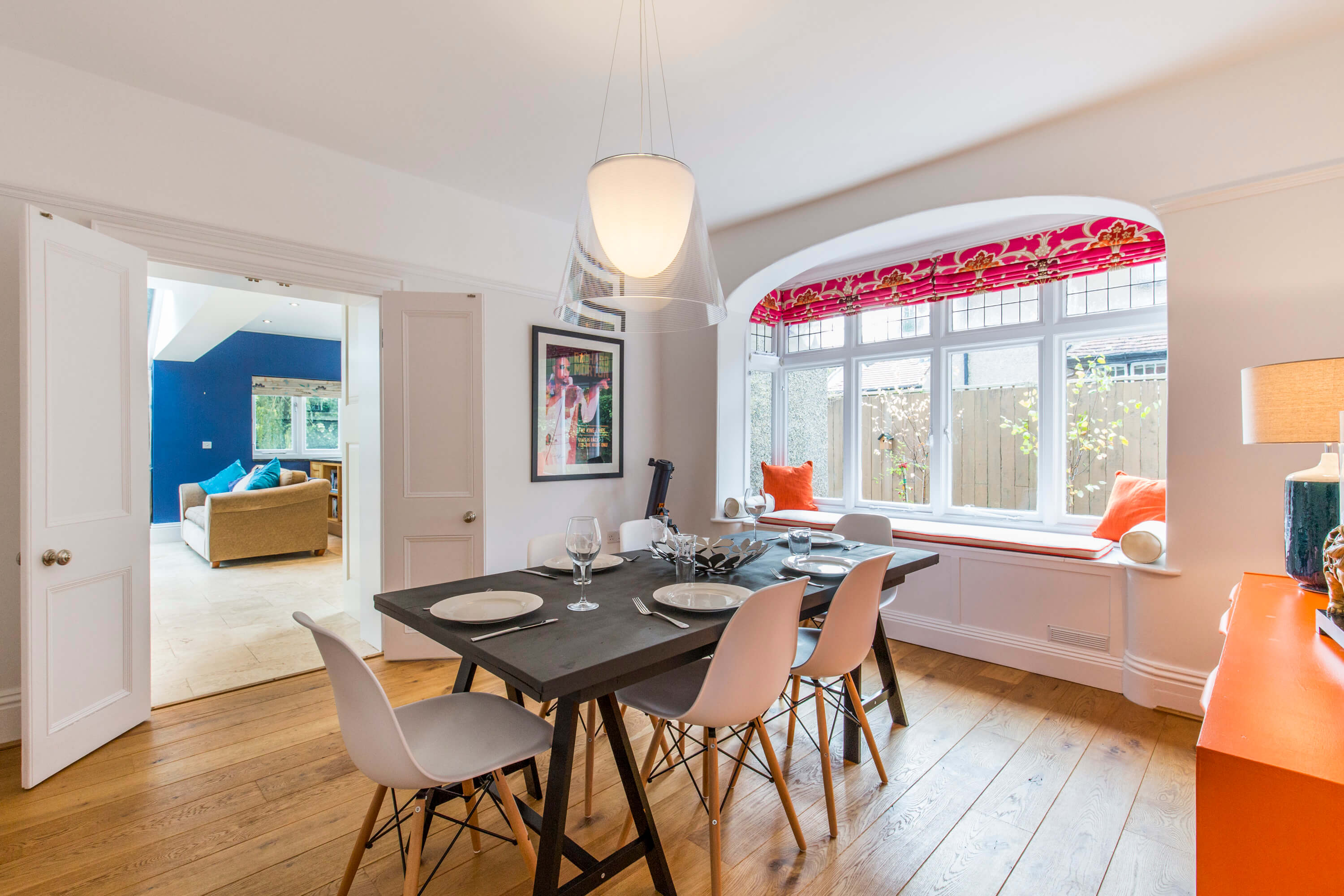 Oak floors and off white walls complement the pops of colour in this busy family dining room