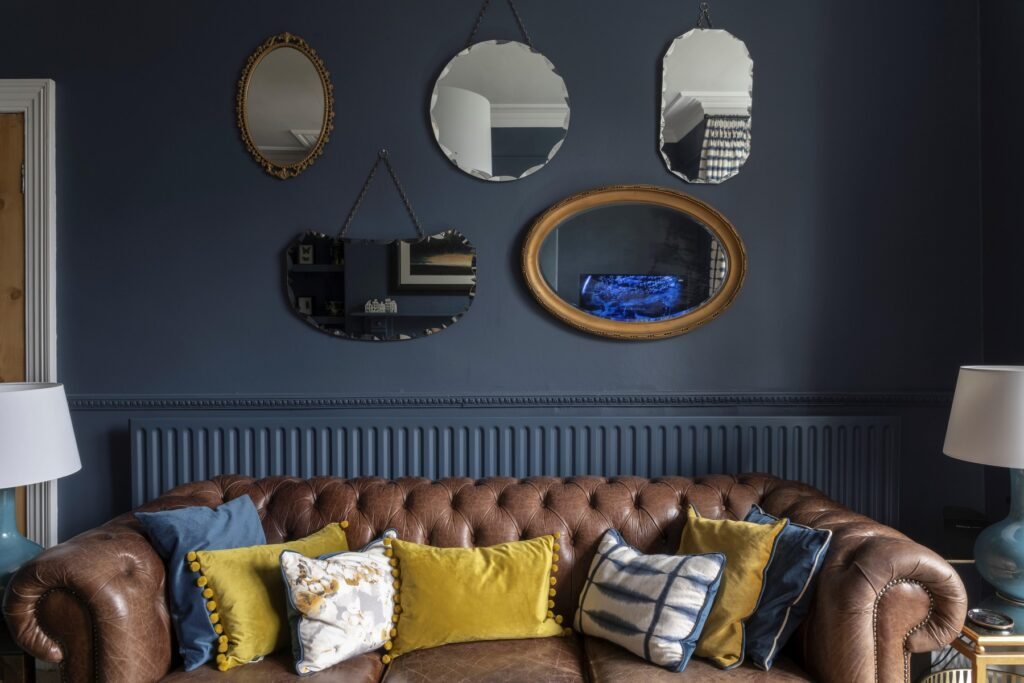 A collection of antique mirrors above a well loved Chesterfield makes for a cosy sitting room