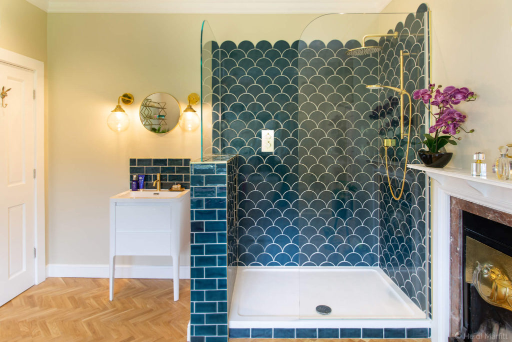 Teal scalloped tiles and brass taps and shower bring personality and style to this generous en suite bathroom
