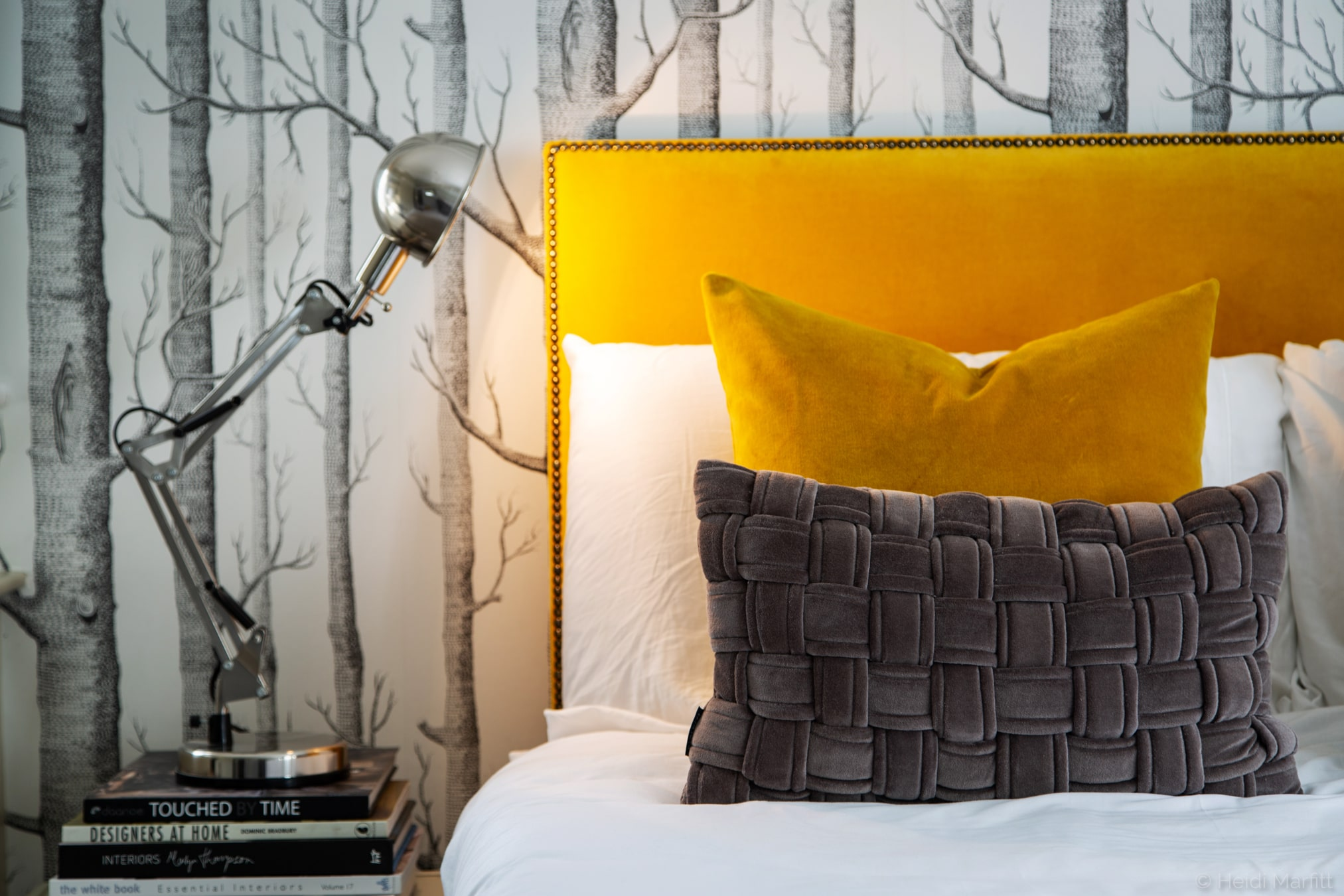 Cole & Sons Woods wallpaper ties together a monochromatic scheme, punctuated by this mustard headboard