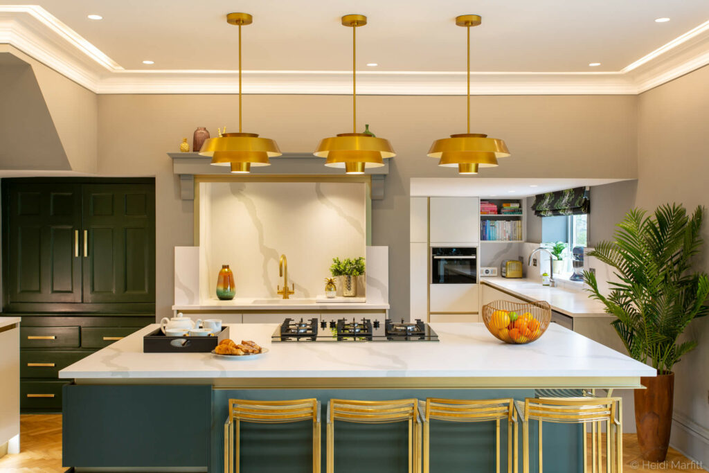 Gold trim adds interest to this inky green island and complements the gold handles and pendant lights