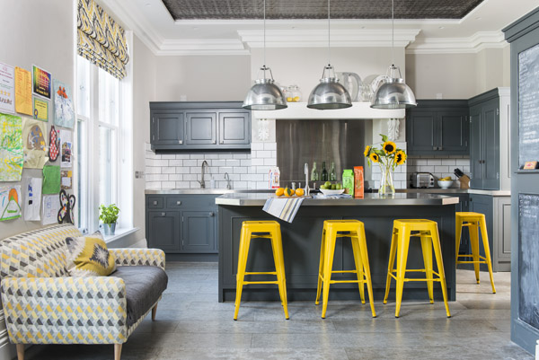 Concrete floors, stainless steel countertops and pops of colour mean this kitchen has plenty of personality