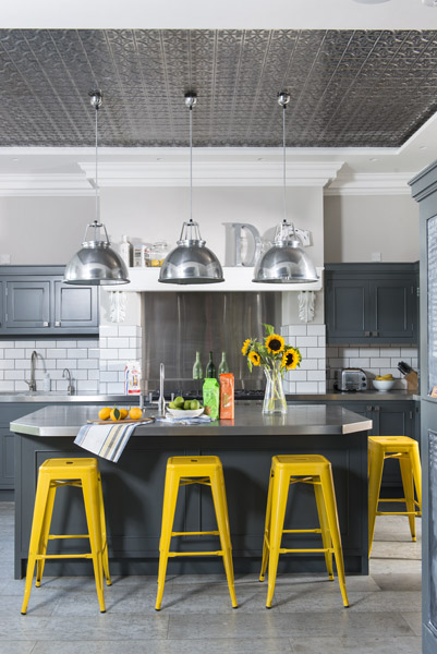 Vibrant yellow stools add a jolt of colour to this industrial style kitchen