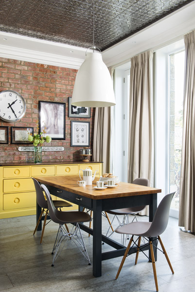 A tin tiled ceiling adds a dash of glamour to this industrial style dining area