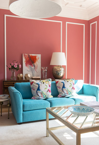 Rich coral walls and a turquoise sofa give personality and life to this family home