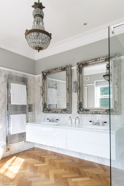 Two oversized mirrors bring drama to this elegant double sink