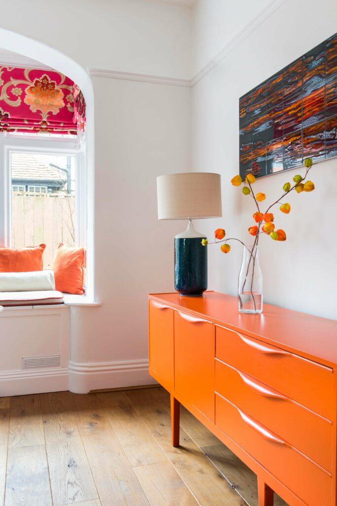 A G plan sideboard was painted a vibrant orange to complement the Designers' Guild blind
