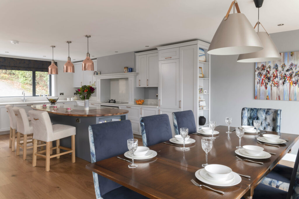 This elegant kitchen is enlivened by copper lights over the island and beautiful artwork over the dining table