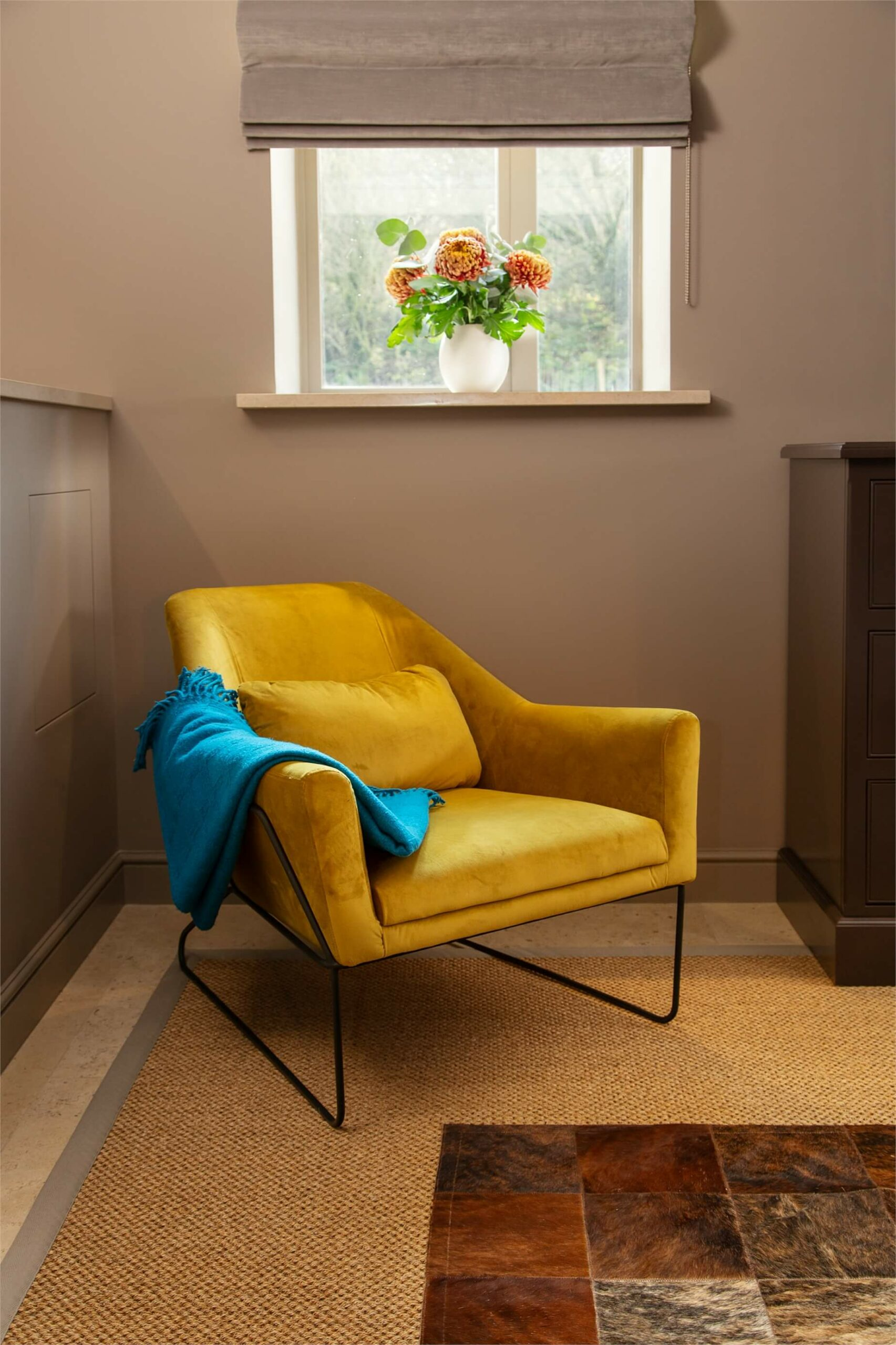 A vibrant chair complements this hide rug in a corner of this luxurious bedroom