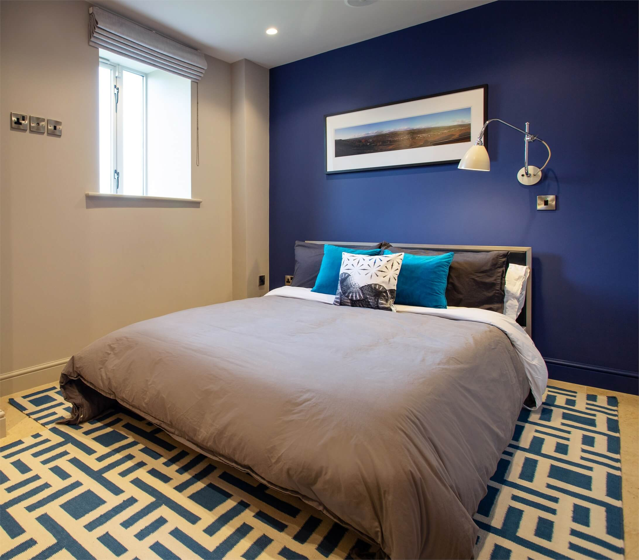 A bespoke Jennifer Manners rug adds interest to this spare bedroom