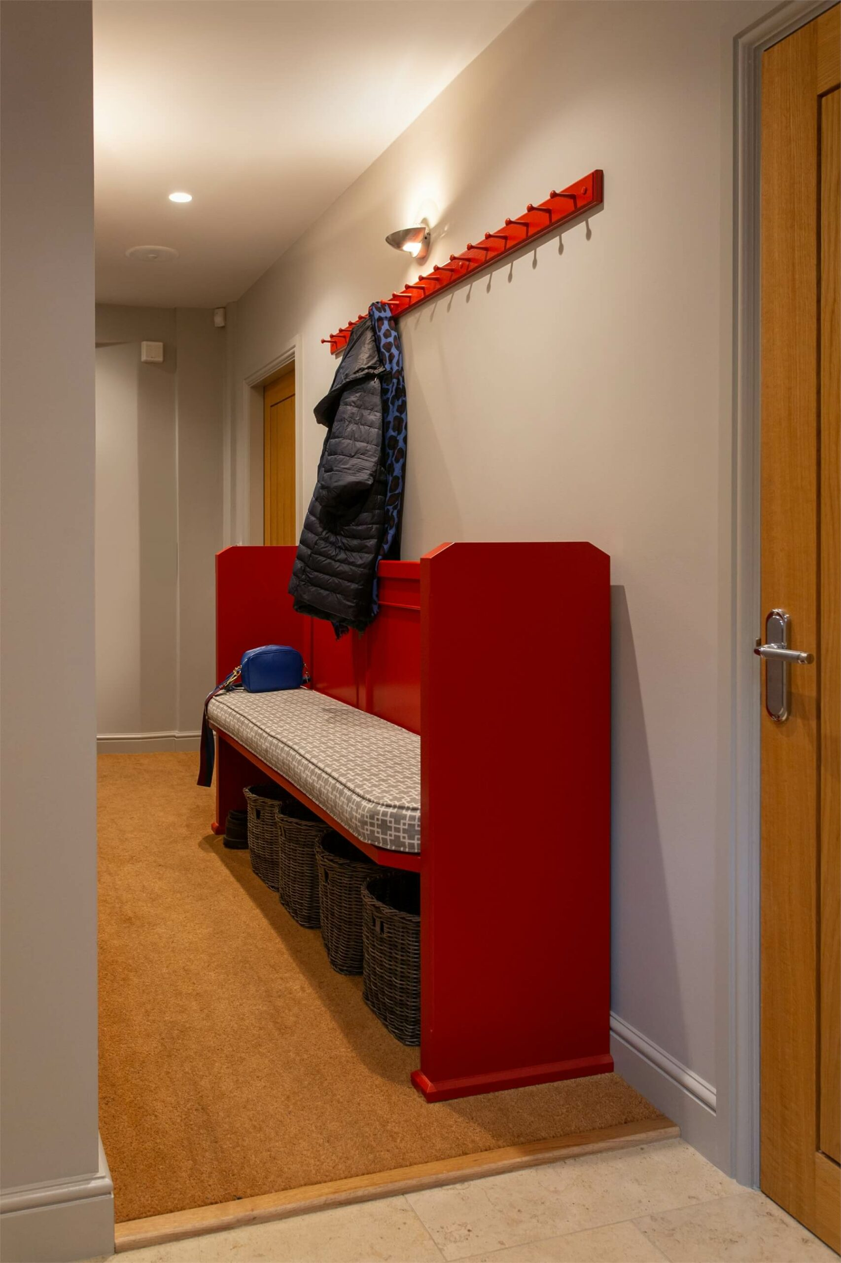 A vibrant red pew is a practical way to add personality and storage to a narrow hallway