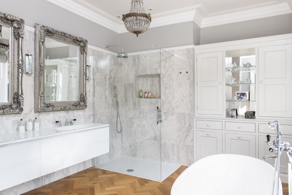 Parquet flooring perfectly complement the marble tiles in this glamorous en suite bathroom